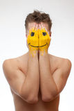 Man hiding his face under smile mask Royalty Free Stock Images