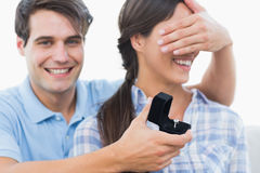 Man hiding his girlfriend eyes and offering her an engagement ri Royalty Free Stock Images