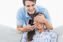 Man hiding his girlfriends eyes and offering her an engagement r Stock Photo