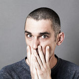 Man hiding his mouth with hands for question and anxiety Royalty Free Stock Photography