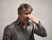 Man hiding his nose Stock Photo
