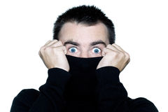 Man hiding his turtle polo neck schock surprised. Caucasian man portrait expressing portrait on studio isolated white background Royalty Free Stock Images
