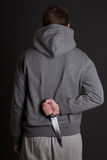 Man hiding knife behind his back over grey Stock Photos