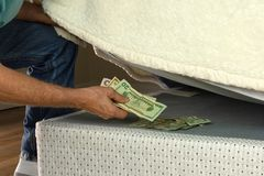 Man hiding money under his mattress because he doesn`t trust banks Royalty Free Stock Images