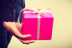 Man hiding pink gift box with ribbon behind back Royalty Free Stock Photography