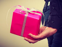 Man hiding pink gift box with ribbon behind back Royalty Free Stock Images