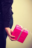Man hiding pink gift box with ribbon behind back Stock Photo
