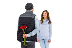 Man hiding a rose behind his back from his woman Royalty Free Stock Photography