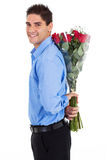 Man hiding roses. Young man hiding bunch of red roses behind his back Royalty Free Stock Photography