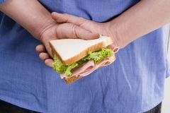 Man hiding sandwich. On his back Royalty Free Stock Photo