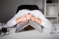 Man hiding under laptop Stock Photography