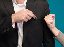 Man hiding wedding ring, woman showing him a fist Stock Image
