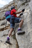 Man in the high of the mountain doing a via ferrata. In Spain Royalty Free Stock Image