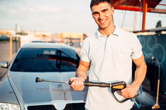 Man with high pressure washer on car wash station. Hand carwashing Royalty Free Stock Images