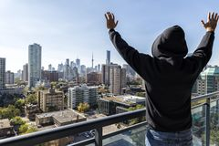 Man on high rise balcony. Man on a high rise building balcony overlooking the city, with hands outstretched. Expressing his joy of life Royalty Free Stock Photography