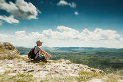 Man hiker with backpack relaxing on top of a mountain Royalty Free Stock Photography