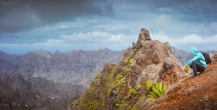 Man hiker with backpack sitting on the mountain top and looking down to the valley. Stunning arid landscape on Santo. Antao island, Cabo Verde Royalty Free Stock Images