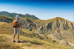 Man hiker with backpack standing against badland stock images