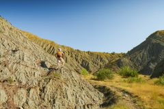 Man hiker with backpack standing in a badland canyon Stock Photo
