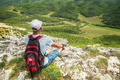 Man hiker with backpack on top of a mountain Royalty Free Stock Photo