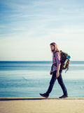 Man hiker with backpack tramping by seaside Royalty Free Stock Photos
