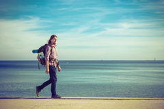 Man hiker with backpack tramping by seaside Stock Photo