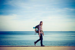 Man hiker with backpack tramping by seaside Royalty Free Stock Photography