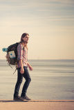 Man hiker with backpack tramping by seaside Stock Images