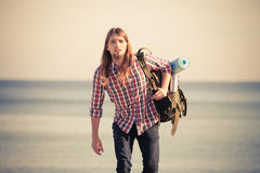 Man hiker with backpack tramping by seaside Royalty Free Stock Image