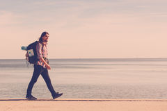 Man hiker with backpack tramping by seaside Stock Photos