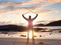 Man hiker with a backpack and trekking pole standing at rocky shore and looking on the evening horizon. Sun flare in the lens Stock Photos