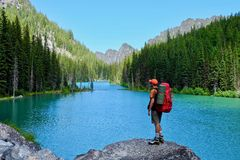 Man hiker backpacker on rocks by alpine lake. Stock Photos