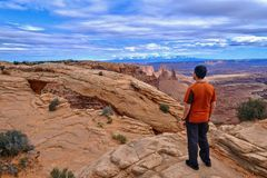 Man hiker on cliff looking at canyon views. Mesa Arch in Canyonlands National Park. La Sal Mountains. Moab. Cedar City. Utah. United States Stock Photos