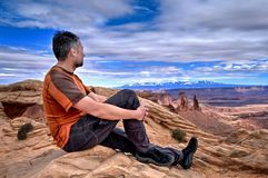 Man hiker on cliff looking at canyon views. Mesa Arch in Canyonlands National Park. La Sal Mountains. Moab. Cedar City. Utah. United States Stock Photography