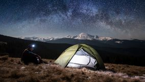 Male tourist have a rest in his camping in the mountains at night under beautiful night sky full of stars and milky way. Man hiker enjoying night scene in his Stock Photos