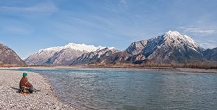 Man hiker on shore of river looking the mountains. Royalty Free Stock Photography