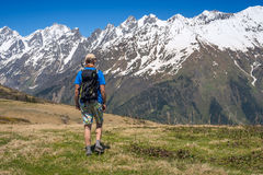 Man hiker goes along alpine meadow to the snow-capped mountain r Stock Photos