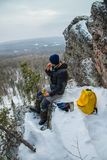 Man hiker have a rest at mountain top, drinking tea and eating during winter adventure. Man hiker have a rest at mountain top, drinking tea and eating during Royalty Free Stock Photos