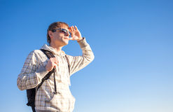 Man hiker holding backpack on a sunny day against a blue sky Stock Photos