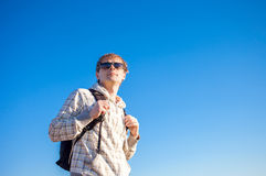 Man hiker holding backpack on a sunny day against a blue sky Royalty Free Stock Photo