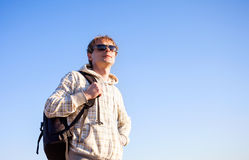 Man hiker holding backpack on a sunny day against a blue sky Stock Photography