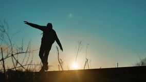 Man hiker homeless person traveler hand to the sides freedom walking by railroad silhouette road. man with a backpack. Going to sunset silhouette against stock footage