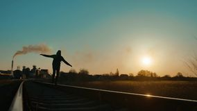 Man hiker homeless person traveler hand to the sides freedom walking by railroad silhouette road. man with a backpack. Going to sunset silhouette against stock video