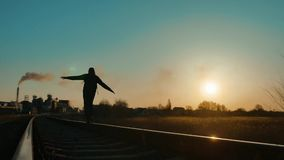 Man hiker homeless person traveler hand to the sides freedom walking by railroad silhouette road. man with a backpack. Going to sunset silhouette against stock video footage