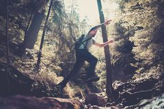 Man hiker jumping across stream. In mountain forest royalty free stock image