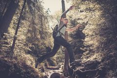 Man hiker jumping across stream. In mountain forest royalty free stock images