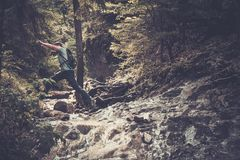 Man hiker jumping across stream Royalty Free Stock Image