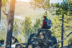 Man hiker with a large backpack sitting on a rock cliff and looking at the sprawling green valley. Freedom in travel. Man tourist hiker with a large backpack stock images