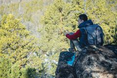 Man hiker with a large backpack sitting on a rock cliff and looking at the sprawling green valley. Freedom in travel. Man tourist hiker with a large backpack stock photography
