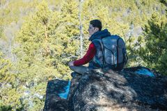 Man hiker with a large backpack sitting on a rock cliff and looking at the sprawling green valley. Freedom in travel. Man tourist hiker with a large backpack royalty free stock photo
